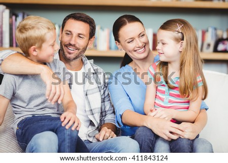 Close-up of happy family sitting on sofa at home - stock photo