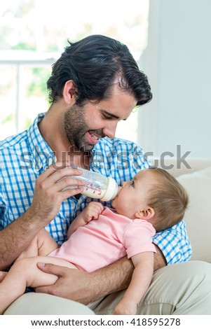 Close-up of happy father feeding milk to son on sofa at home - stock photo