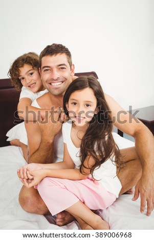 Close-up of happy father with daughter and son on bed at home - stock photo