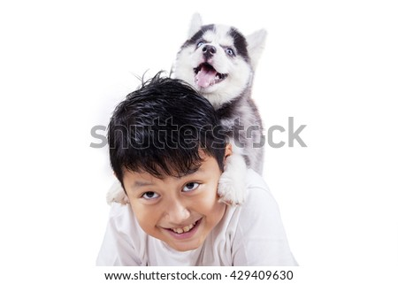 Close up of happy little boy playing in the studio with siberian husky puppy, isolated on white background - stock photo