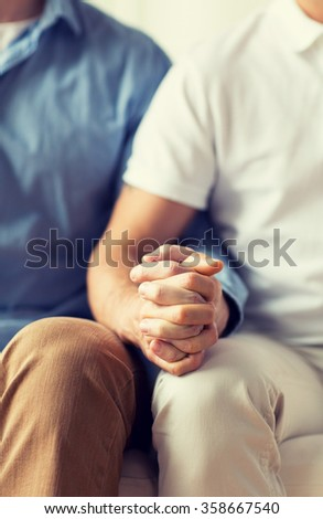 close up of happy male gay couple holding hands - stock photo