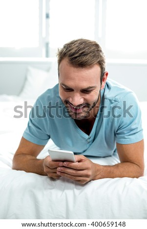 Close-up of happy man using cellphone while lying on bed at home - stock photo