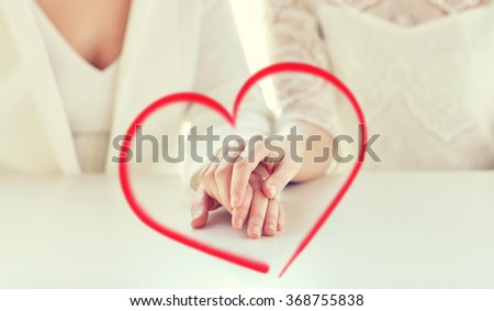 close up of happy married lesbian couple hands