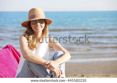 Close-up of happy mature woman enjoying summer vacation while sitting on sandy beach and relaxing.