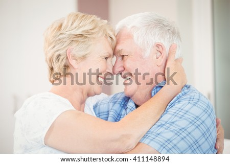 Close-up of happy senior couple embracing in bedroom at home - stock photo