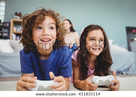 Close-up of happy siblings with controllers playing video game on carpet at home - stock photo