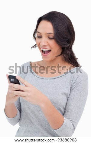 Close up of happy woman reading text message against a white background - stock photo