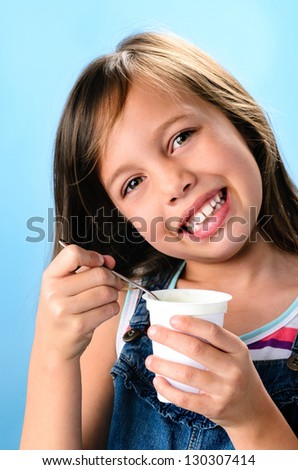 Close up of happy young girl eating healthy food plain yoghurt - stock photo