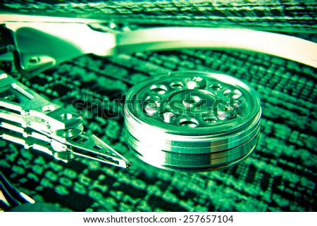 close up of hard disk with green abstract technology reflection