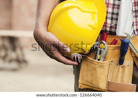 Close-up of hard hat holding by construction worker - stock photo