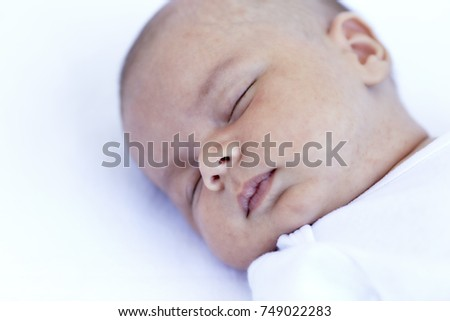 Close up of head of Newborn baby boy sleeping on back on a white blanket