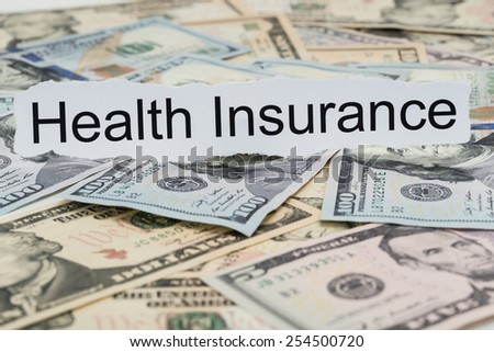 Close-up Of Health Insurance Text On Piece Of Paper With Banknotes - stock photo