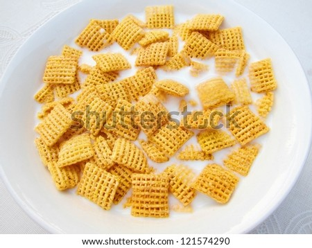 Close-up of healthy appetizing nutritious and delicious breakfast square cornflakes with milk in a white bowl - stock photo