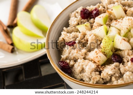 Close up of healthy breakfast oatmeal with apples and cranberries and cinnamon sticks - stock photo