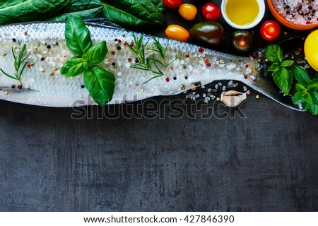 Close up of healthy fish dishes cooking background with space for text. Raw fish with various ingredients on dark vintage board, preparation. Flat lay. Healthy food or diet nutrition concept. - stock photo