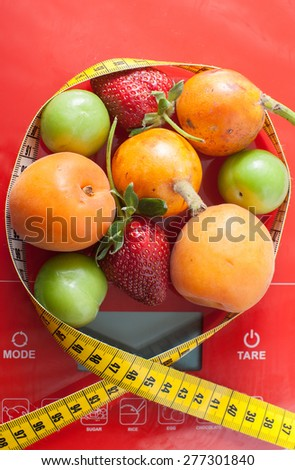 Close up of healthy fruits on a scale surrounded by a tape measure
