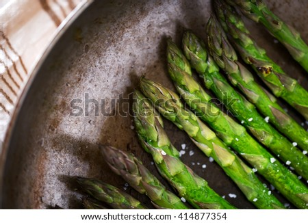 Close-up of healthy frying asparagus with salt on pan