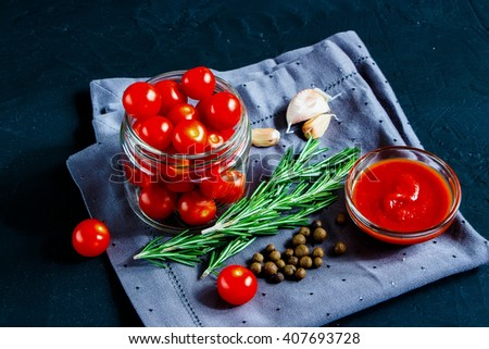 Close up of healthy ingredients for cooking cherry tomato sauce on dark rustic background, selective focus. Vegetarian eating. Fresh harvest from the garden. - stock photo