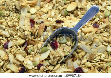 Close up of healthy organic dried fruit and nut granola with a metal scoop - stock photo
