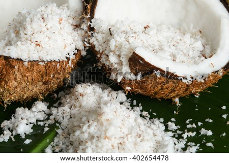 Close up of heap of grated organic coconut in a fresh coconut cut open, isolated on green banana leaf, Kerala India. main ingredient in Indian dishes. - stock photo