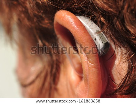 close-up of hearing aid on the woman's ear - stock photo