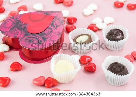 Close up of heart shaped candy box with chocolate candies on a pink background.