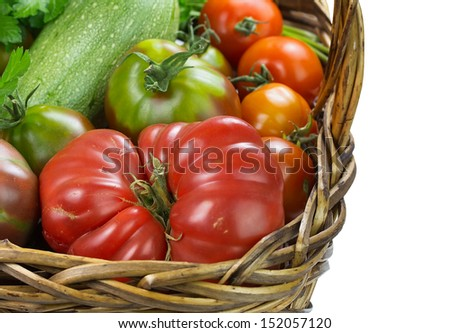 Close-up of heirloom tomatoes and white zucchini in woven basket on white background. - stock photo