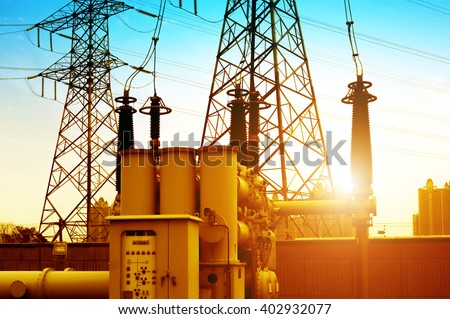 Close-up of high-voltage power substation equipment, evening landscape.