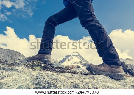 Close-up of hiking shoes on ridge with mountain view in the background. - stock photo