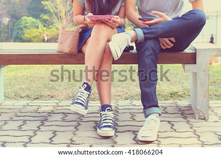 Close up of hipster couple in disinterest moment with smart phones in the outdoor, concept of relationship apathy and isolating using new technology and smartphone addiction - stock photo