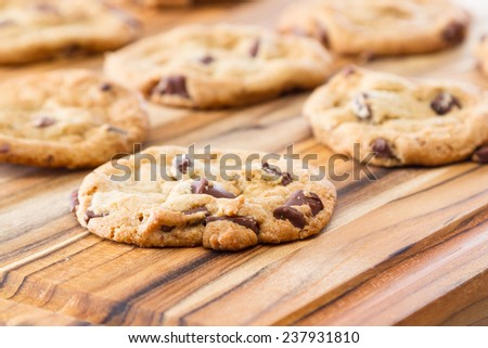 close up of home made chocolate chip cookies on a wooden table - stock photo