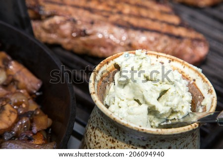 close up of Home made crock of blue cheese steak butter with steaks on the grill in the background - stock photo