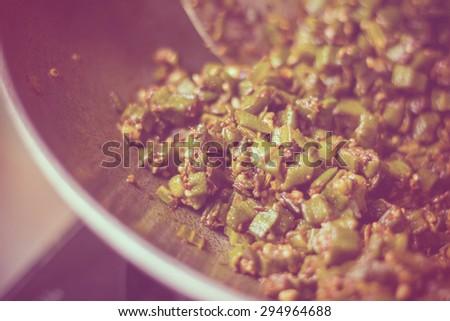 close up of home made masala bhindi or ladyfinger in aluminium karahi - stock photo