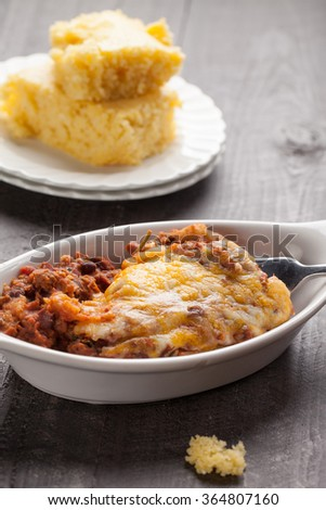 Close up of homemade baked chili in small porcelain bowl with side of cornbread - stock photo