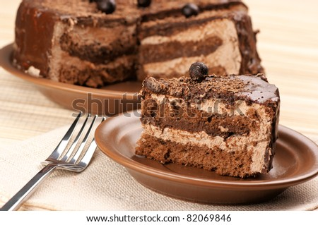 Close-up of homemade chocolate cake and fork on beige background.. - stock photo