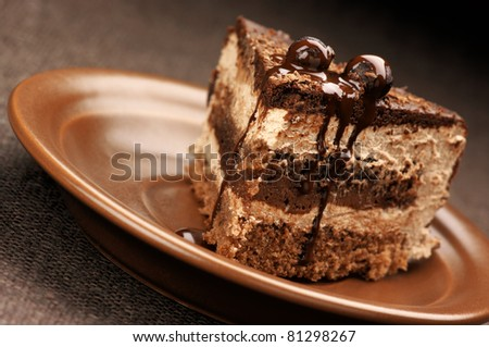 Close-up of homemade chocolate cake in brown ceramic plate.