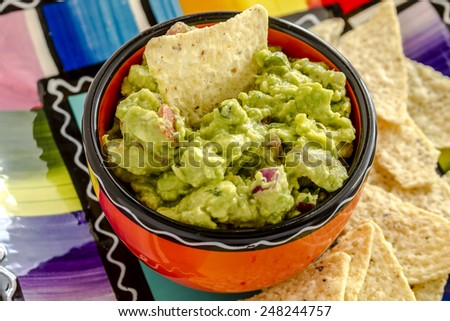 Close up of homemade chunky guacamole in bright orange bowl sitting on colorful plate with white corn tortilla chips