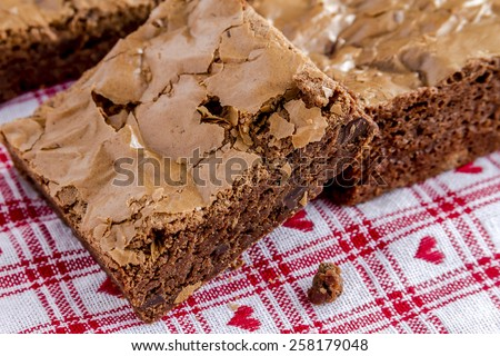 Close up of homemade double chocolate chunk brownies sitting on white checked napkin with red hearts - stock photo