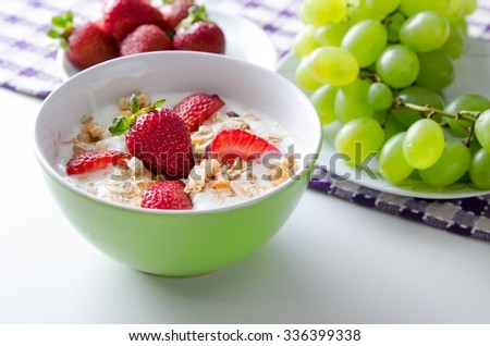 Close up of homemade fruit plate with yogurt, strawberries and granola - stock photo