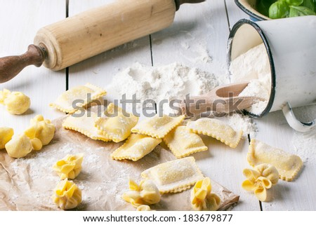 Close up of homemade pasta ravioli and perle on wooden table with metal mug of flour. See series