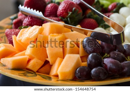 Close up of hors d'oeuvres of assorted cheeses and fruits - stock photo