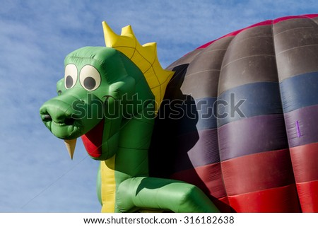 Close up of hot air balloon with dragon shaped surrounding balloon on ground before take off - stock photo