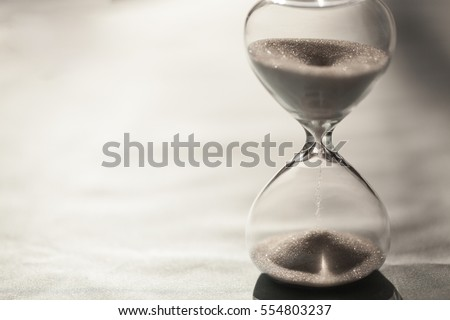 Close up of hourglass clock. Hourglass time passing concept for business deadline, urgency and running out of time