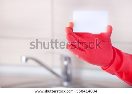 Close up of house cleaner's hand with safety glove showing blank business card against kitchen sink and tiles in background - stock photo