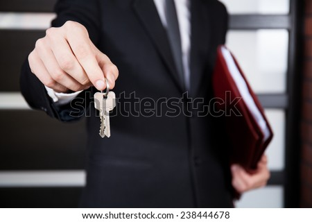 Close-up of house keys held by house agent - stock photo