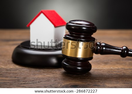 Close-up Of House Model With Gavel On Wooden Table