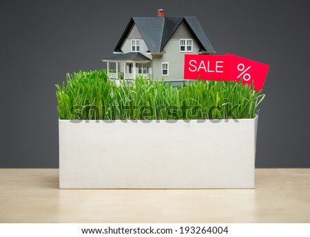 Close up of house model with green grass and sale tablet on grey background. Concept of property and sales - stock photo