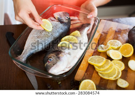 Close-up of housewife putting pieces of lemon in fish at  kitchen