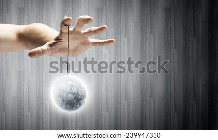 Close up of human hand and items hanging on fingers. Elements of this image are furnished by NASA - stock photo
