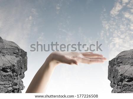 Close up of human hand between mountain gap - stock photo